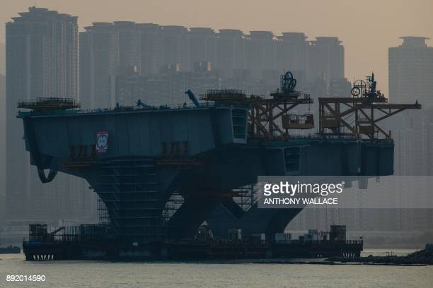 In this picture taken on December 11 a construction worker is seen on a strut of the Hong KongZhuhaiMacau Bridge in Hong Kong Billed as the world's...