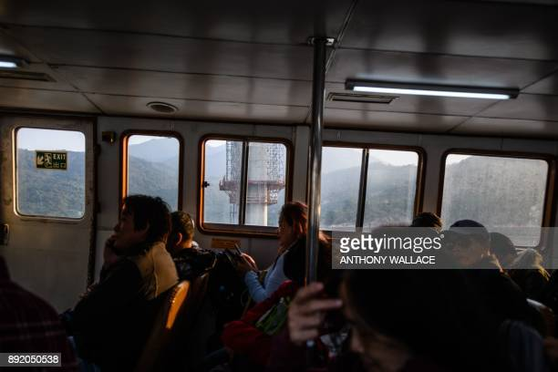 In this picture taken on December 11 commuters on a ferry pass a section of the Hong KongZhuhaiMacau Bridge in Hong Kong Billed as the world's...