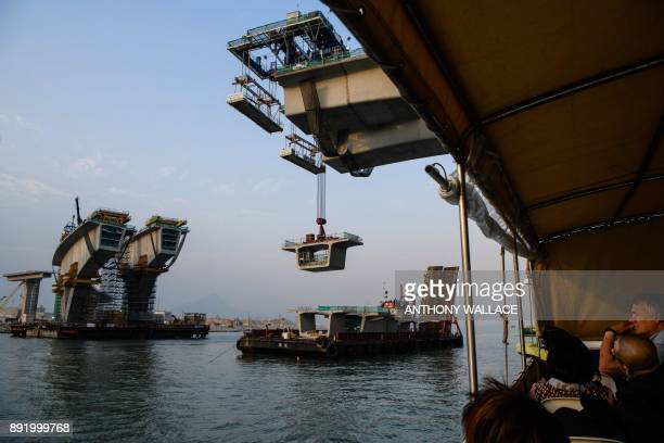 In this picture taken on December 11 commuters on a ferry pass an incomplete section of the Hong KongZhuhaiMacau Bridge in Hong Kong Billed as the...
