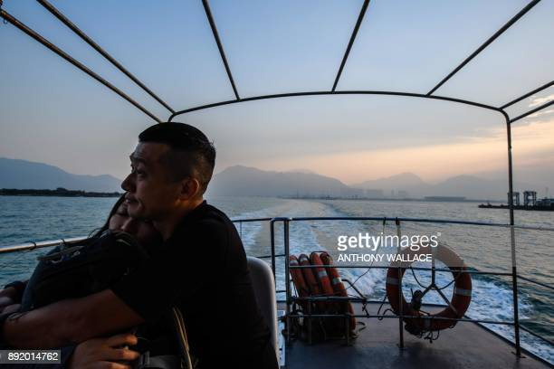 In this picture taken on December 11 commuters on a ferry sail away from the Hong KongZhuhaiMacau Bridge in Hong Kong Billed as the world's longest...