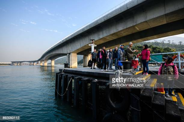 In this picture taken on December 11 commuters prepare to board a ferry under a section of the Hong KongZhuhaiMacau Bridge in Hong Kong Billed as the...