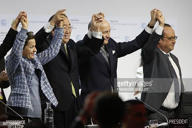 In this picture taken on December 12, 2015 Foreign Affairs Minister and President-designate of COP21 Laurent Fabius , raises hands with Secretary...