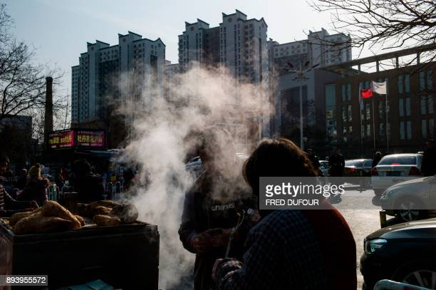 In this picture taken on December 13 a man buys steamed buns from a street vendor on a cold day in Baoding As temperatures dipped below freezing in a...