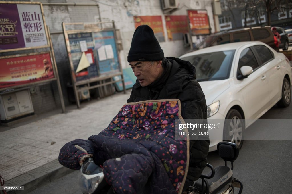 In this picture taken on December 13, 2017, a man commutes along a street on a cold day in Baoding. As temperatures dipped below freezing in a northern Chinese village, a group of parka-clad women tried to stay warm as they played mahjong around a small gas stove in a grocery store. / AFP PHOTO / FRED DUFOUR / To go with AFP story China-Energy-Pollution , Focus by Julien Girault