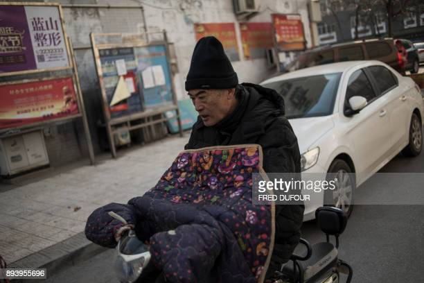 In this picture taken on December 13 a man commutes along a street on a cold day in Baoding As temperatures dipped below freezing in a northern...