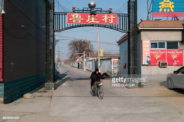 In this picture taken on December 13 a man rides his bicycle in Niezhuang village in the Baoding municipality about 150 kilometres south of Beijing...