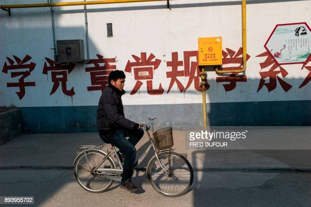 In this picture taken on December 13 a man rides his bicycle past gas pipes in Niezhuang village in the Baoding municipality about 150 kilometres...