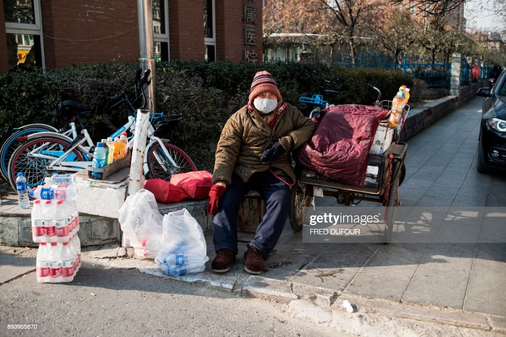 In this picture taken on December 13, 2017, a man sells goods near the hospital on a cold day in Baoding. As temperatures dipped below freezing in a northern Chinese village, a group of parka-clad women tried to stay warm as they played mahjong around a small gas stove in a grocery store. / AFP PHOTO / FRED DUFOUR / To go with AFP story China-Energy-Pollution , Focus by Julien Girault
