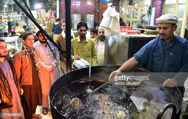 In this picture taken on December 13 a Pakistani cook grills kebabs while customers look on at the Tory Kebab House in Namak Mandi in Peshawar The...