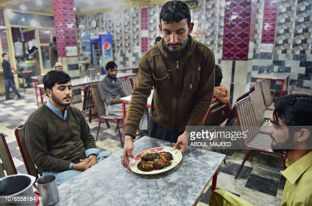 In this picture taken on December 13 a Pakistani man serves customers a plate of kebabs at the Tory Kebab House in Namak Mandi in Peshawar The sweet...