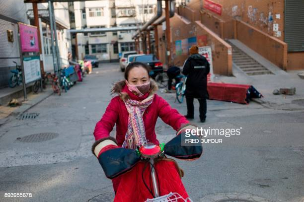 In this picture taken on December 13 a woman commutes on a street on a cold day in Baoding As temperatures dipped below freezing in a northern...