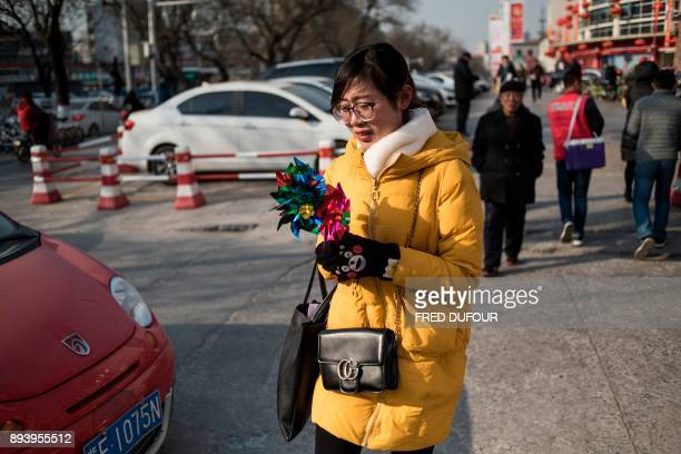 In this picture taken on December 13 a woman holds a windwheel as she walks along a street on a cold day in Baoding As temperatures dipped below...