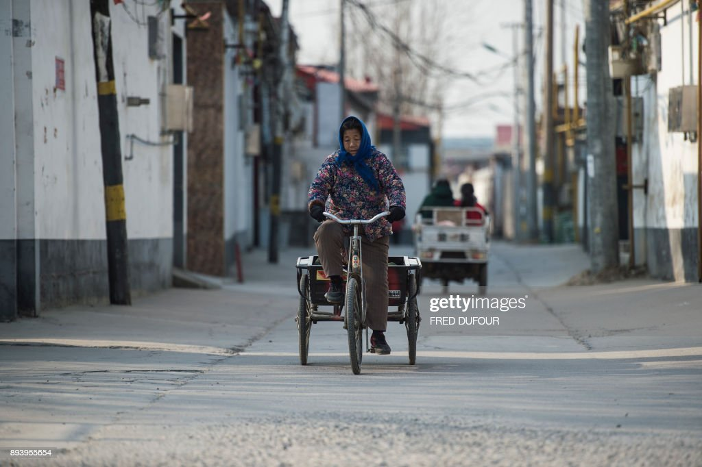 In this picture taken on December 13, 2017, a woman rides her bicycle in Niezhuang village, in the Baoding municipality about 150 kilometres south of Beijing. As temperatures dipped below freezing in a northern Chinese village, a group of parka-clad women tried to stay warm as they played mahjong around a small gas stove in a grocery store. / AFP PHOTO / FRED DUFOUR / To go with AFP story China-Energy-Pollution , Focus by Julien Girault