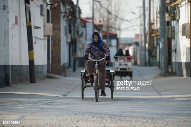 In this picture taken on December 13 a woman rides her bicycle in Niezhuang village in the Baoding municipality about 150 kilometres south of Beijing...
