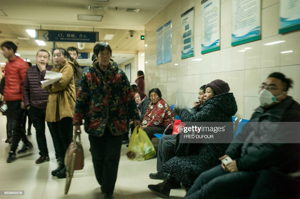 In this picture taken on December 13, 2017, patients wait in a hospital in Baoding. As temperatures dipped below freezing in a northern Chinese village, a group of parka-clad women tried to stay warm as they played mahjong around a small gas stove in a grocery store. / AFP PHOTO / FRED DUFOUR / To go with AFP story China-Energy-Pollution , Focus by Julien Girault