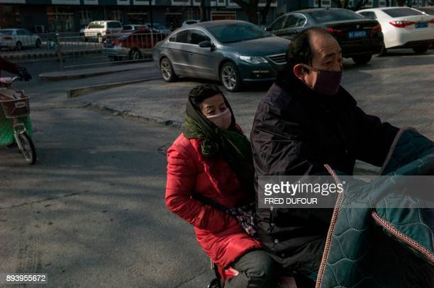 In this picture taken on December 13 people commute on a street on a cold day in Baoding As temperatures dipped below freezing in a northern Chinese...