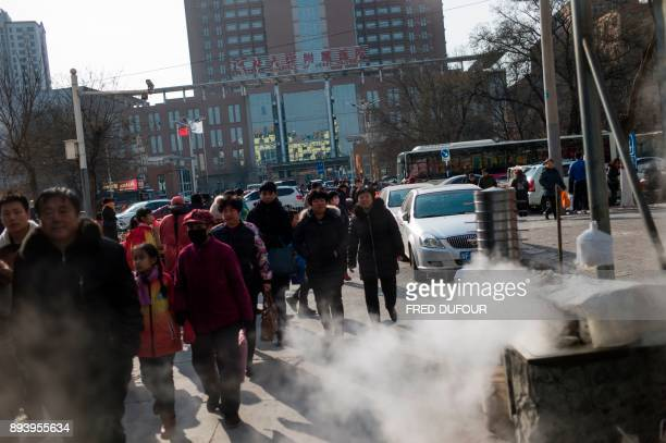 In this picture taken on December 13 people walk past steamed buns on a cold day in Baoding As temperatures dipped below freezing in a northern...