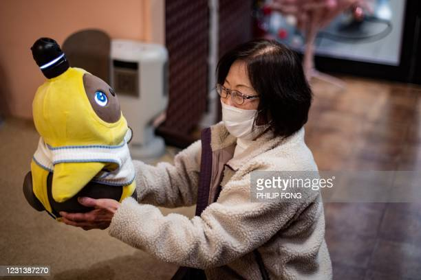 In this picture taken on December 20, 2020 shows a diner holding a Lovot robot in a cafe in Kawasaki. - Smart home assistants like Amazon's Alexa...