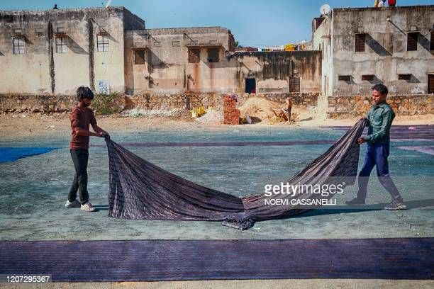 In this picture taken on December 29, 2019 artisans they lie fabrics on the ground to dry after a synthetic indigo dye process in Bagru village, some...