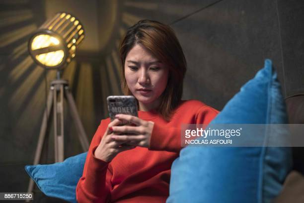 In this picture taken on December 5 2017 Jia Xinru browses her smartphone in her office lounge in Beijing When Jia Xinru needed to borrow money to...