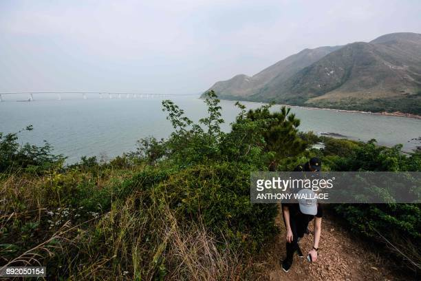 In this picture taken on December 5 a couple hike on the Lantau fishing village of Tai O which overlooks the Hong KongZhuhaiMacau Bridge in Hong Kong...