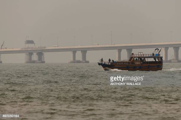 In this picture taken on December 5 passengers of a junk sail past a section of the Hong KongZhuhaiMacau Bridge in Hong Kong Billed as the world's...