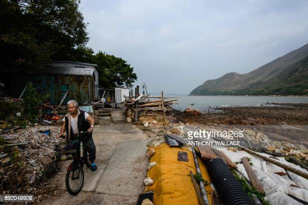 In this picture taken on December 5 resident Wong Kam Fook prepares to ride his bicycle at the Lantau fishing village of Tai O which overlooks the...