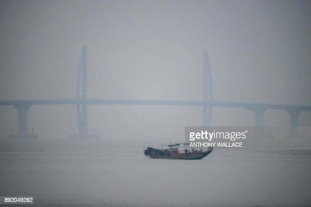 In this picture taken on December 6 a boat is seen in front of a section of the Hong KongZhuhaiMacau Bridge in Macau Billed as the world's longest...