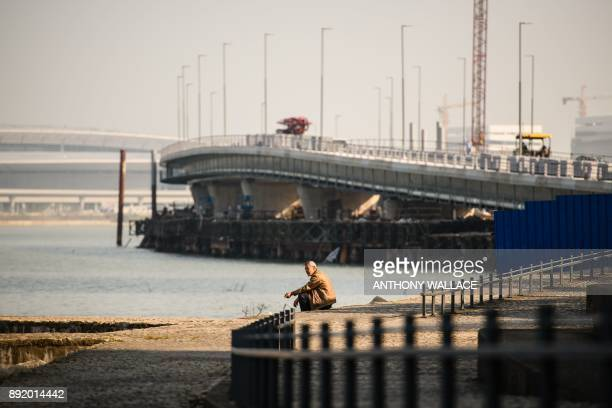 In this picture taken on December 6 a man smokes as he rests in front of a section of the Hong KongZhuhaiMacau Bridge in Macau Billed as the world's...