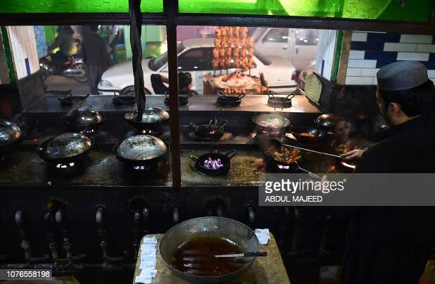 In this picture taken on December 6 a Pakistani man cooks grilled meat at the Charsi Tikka restaurant in Namak Mandi in Peshawar The sweet aroma of...