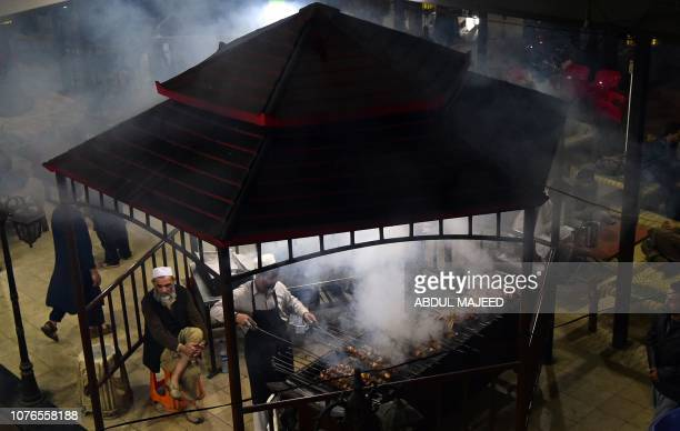 In this picture taken on December 6 a Pakistani man cooks grilled meat on a barbeque at the Charsi Tikka restaurant in Namak Mandi in Peshawar The...