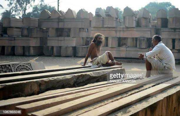 In this picture taken on December 6 an Indian sadhu sits on stone slabs being prepared for a proposed Hindu temple at Ram Janmabhoomi Nyas workshop...