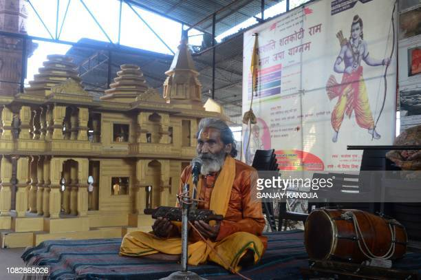 In this picture taken on December 6 an Indian sadhu worships as he sits next to a model of the proposed Hindu temple at Ram Janmabhoomi Nyas workshop...