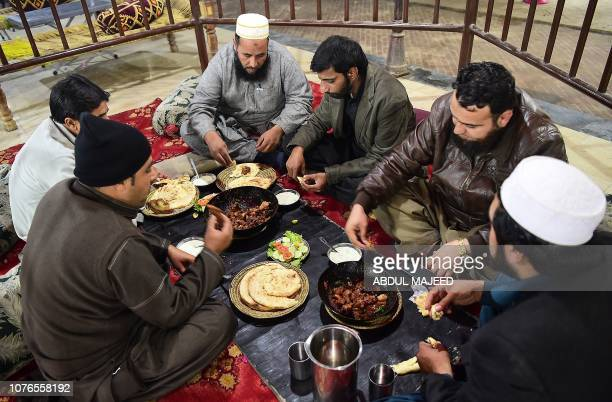 In this picture taken on December 6 Pakistani customers eat grilled meat at the Charsi Tikka restaurant in Namak Mandi in Peshawar The sweet aroma of...