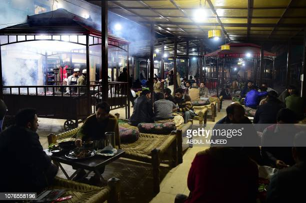 In this picture taken on December 6 Pakistani patrons enjoy eating grilled meat cooked on a barbeque at the Charsi Tikka restaurant in Namak Mandi in...