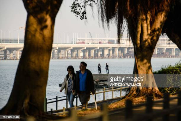 In this picture taken on December 6 pedestrians walk past a section of the Hong KongZhuhaiMacau Bridge in Macau Billed as the world's longest sea...