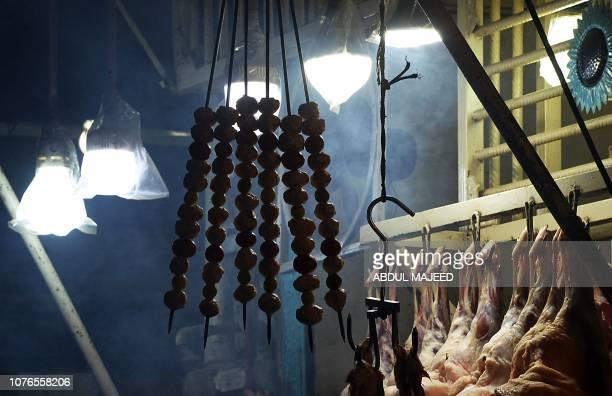 In this picture taken on December 6 skewers of lamb hang at a Charsi Tikka restaurant in Namak Mandi in Peshawar The sweet aroma of mutton smoke...