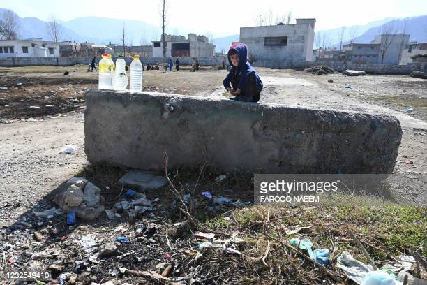In this picture taken on February 11 a boy sits on a concrete structure at the site of the demolished compound of slain former Al-Qaeda leader Osama...