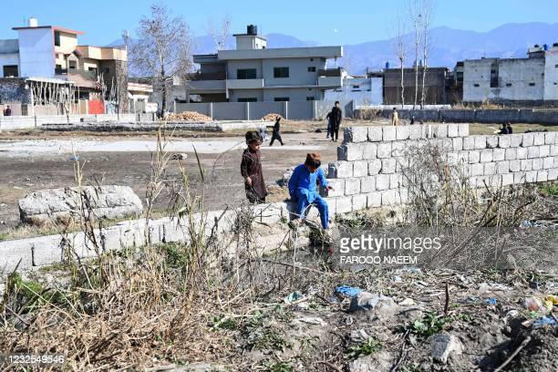 In this picture taken on February 11 boys play at the site of the demolished compound of slain former Al-Qaeda leader Osama bin Laden, in northern...