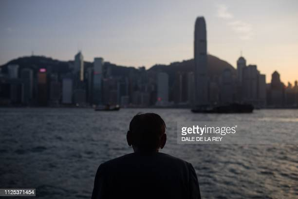 In this picture taken on February 16 a man looks across the harbour towards the city skyline on Hong Kong island Hong Kongs economy grew at its...