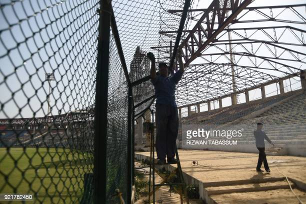 In this picture taken on February 17 Pakistani labourers constructs a fence at the National Cricket Stadium in Karachi Pakistan will launch the third...