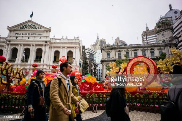 In this picture taken on February 2 pedestrians walk in Senado Square past views of the 16thcentury Portuguese complex 'Santa Casa da Misericórdia de...