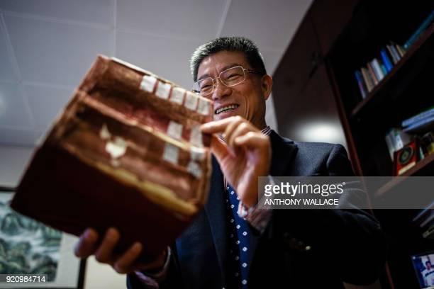 In this picture taken on February 2 professor Lei Heong Iok holds what he calls 'his treasure' a Portuguese dictionary in his office at the Macau...