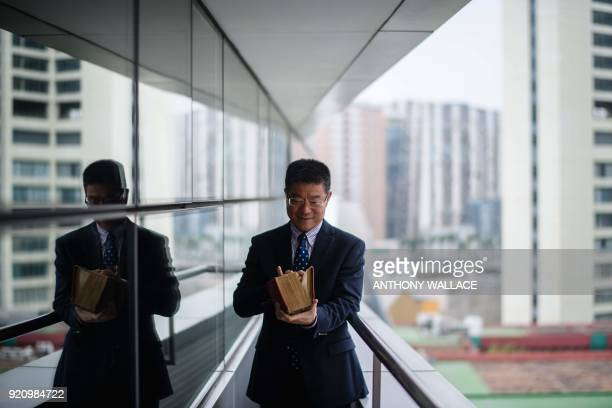 In this picture taken on February 2 professor Lei Heong Iok holds what he calls 'his treasure' a Portuguese dictionary on the balcony of his office...