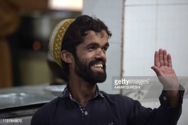 In this picture taken on February 22 Pakistani waiter Rozi Khan who resembles US actor Peter Dinklage waving to customers at Dilbar Hotel in...