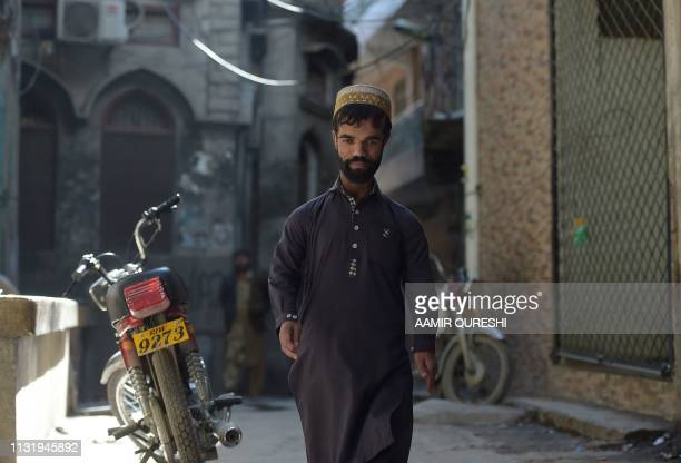In this picture taken on February 22 Pakistani waiter Rozi Khan who resembles US actor Peter Dinklage walks on a street in Rawalpindi Rozi Khan had...