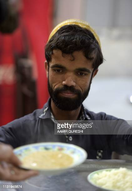 In this picture taken on February 22 Rozi Khan a 25yearold Pakistani waiter who resembles US actor Peter Dinklage prepares to serve food to customers...