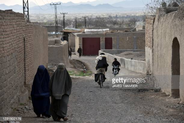 In this picture taken on February 22 women wearing burqas walk along a road in the Arghandab district of Kandahar province. - The Taliban are...