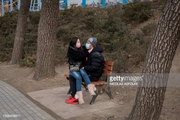 TOPSHOT In this picture taken on February 25 a couple wearing protective facemasks as a preventative measure against the COVID19 coronavirus share a...
