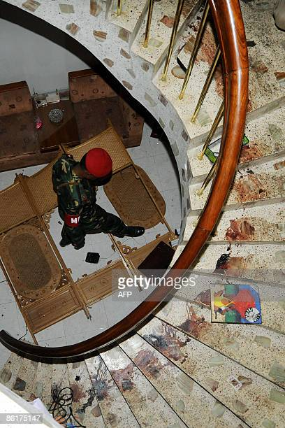 In this picture taken on February 28 a Bangladeshi military policeman sifts through wreckage at the foot of a blood streaked staircase at the house...
